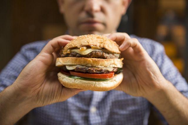 Hombre sosteniendo una hamburguesa