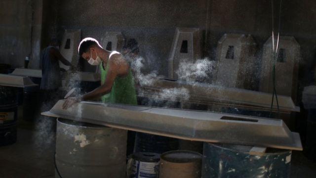 Trabalhador prepara caixão em fábrica, em meio ao surto da doença coronavírus (COVID-19), em Nova Iguaçu, Rio de Janeiro, Brasil, 12 de abril de 2021.