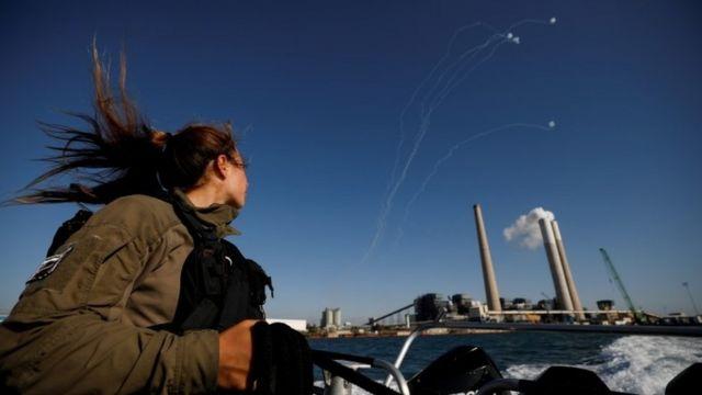 Uma soldado israelense observa enquanto o sistema anti-míssil de Israel, o Domo de Ferro, intercepta foguetes lançados da Faixa de Gaza