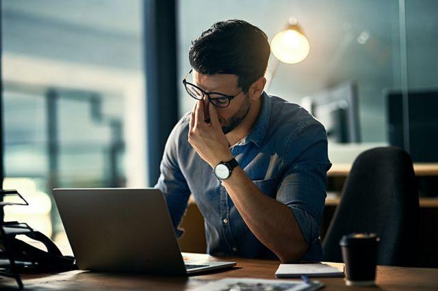 Un hombre agotado frente a una laptop