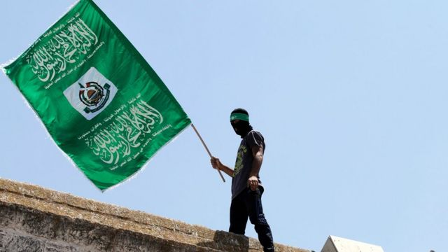 This file photo taken on July 03, 2015 shows a Palestinian man waving the green flag of the Islamist movement Hamas during a demonstration outside the Dome of the Rock at the Al-Aqsa Mosque compound in Jerusalem.