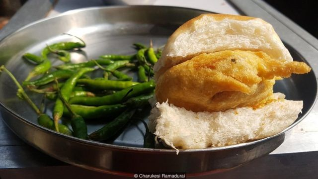 Vada pav is a deep-fried potato patty served on a soft bread roll with spicy green chilli