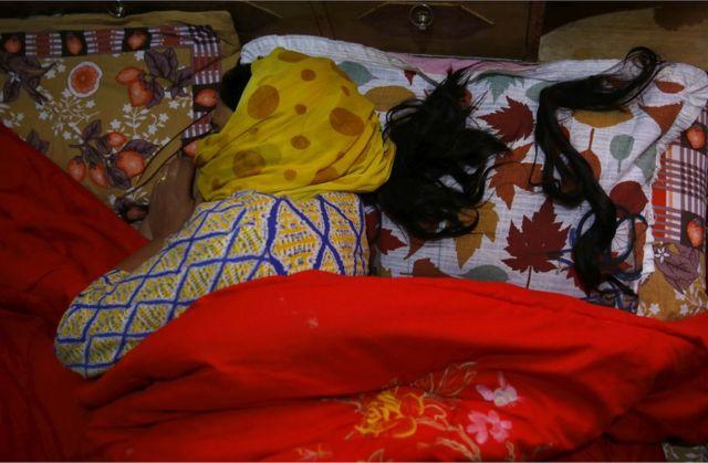 Mwanamke aliyekatwa nywele amelala kitandani kando na nywele yake iliyokatwa
