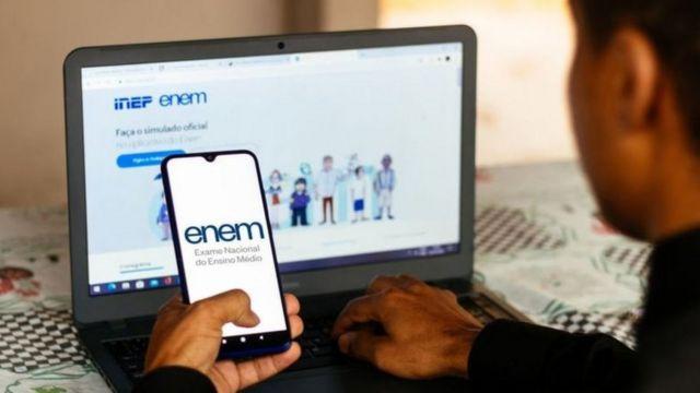 Jovem segura celular enquanto se conecta a site do Enem