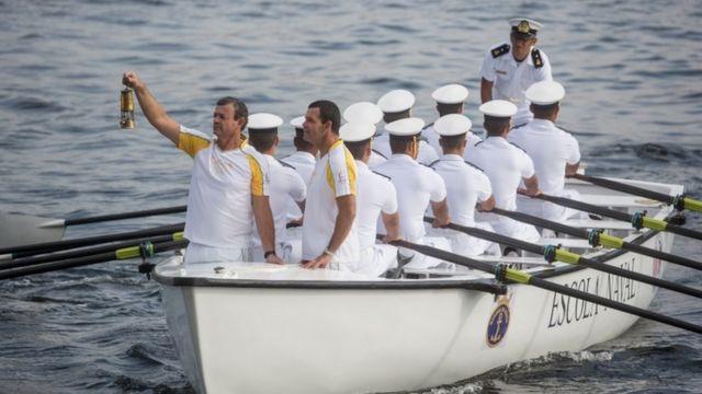 セーリングの五輪メダリスト、ラルス・グラエル氏が聖火の火種が入ったランタン掲げ、ブラジル海軍のボートに乗ってリオに到着した(3日)