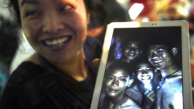 Mulher segura tablet com imagem de meninos vivos no interior de caverna na Tailândia levou alegria a tailandeses e ao mundo -