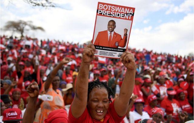 Un partisan du Parti démocratique du Botswana (BDP) brandit une affiche lors d'un rassemblement de campagne électorale à Moshupa, le village natal de Mokgweetsi Masisi, président du Botswana et chef du BDP, le 22 octobre 2019.