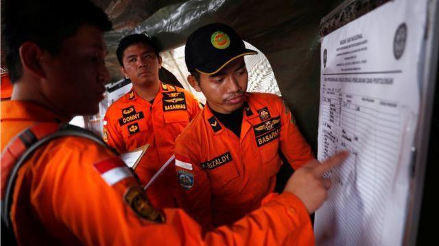 Indonesian rescue team members update a manifest chart