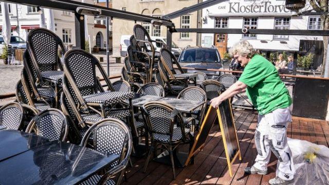 Cadeiras e mesas preparadas para jantares ao ar livre em restaurante em Aalborg, Dinamarca