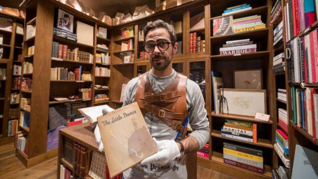 """Un hombre sostiene una copia de la primera edición de """"El principito""""."""