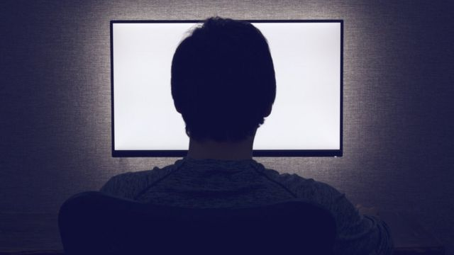 silueta čoveka pred monitorom