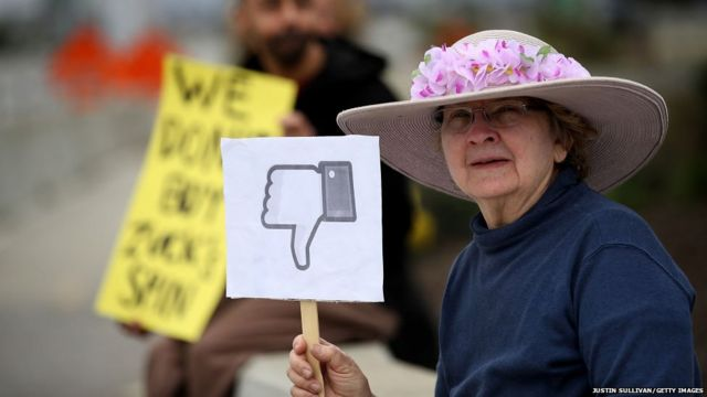 A protester with the group 'Raging Grannies' holds a sign during a demonstration outside of Facebook headquarters on April 5, 2018 in Menlo Park, California.