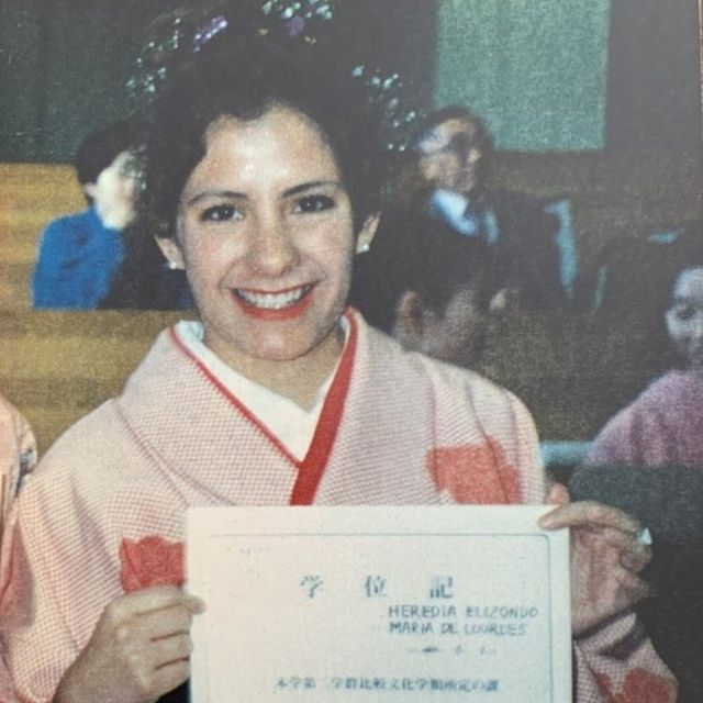 Lourdes holds up her graduation certificate