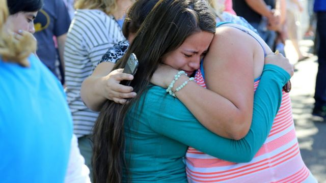 A woman is comforted as friends and family wait for students at the local fairground
