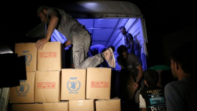 Workers unload parcels of aid to deliver to the Syrian rebel-held town of Darayya
