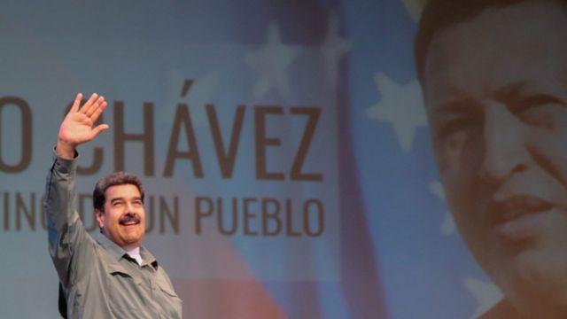 Nicolás Maduro ante un cartel de Hugo Chávez