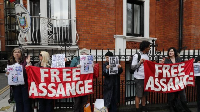 Pro-Assange demonstrators stand with placards after Wikileaks founder Julian Assange addressed the media from the balcony of the Embassy of Ecuador in London