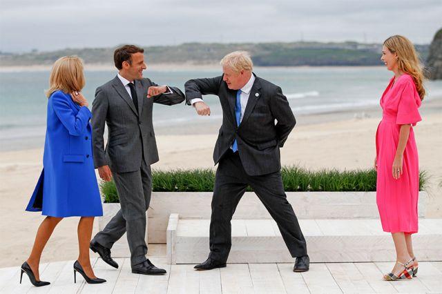 """英国首相约翰逊与法国总统马克龙行疫情下的""""碰肘礼"""",相互致意,他们的夫人凯莉·约翰逊(右)和布丽吉特·马克龙(左)在一旁看着。全球冠状病毒疫苗接种和气候变化将成为七国领导人峰会的重点。"""