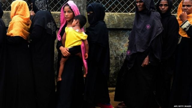 shows Rohingya refugees waiting in line to register at the Kutupalong refugee camp after arriving in Bangladesh.