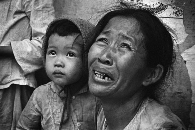 A weeping mother and her young child