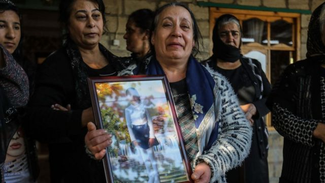 Women hold portrait of a girl killed by the Arman army