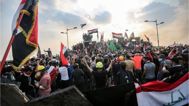 """Iraqi protesters wave national flags as they stand atop concrete barriers across the capital Baghdad""""s al-Jumhuriya bridge which connects between Tahrir Square and the high-security Green Zone, hosting government offices and foreign embassies, on October 29, 2019 during the ongoing anti-government protests."""