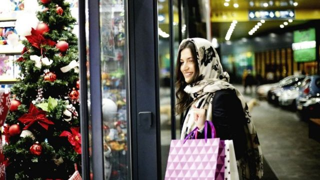 A smiling young woman doing her Christmas shopping, bags in hand, looks at a shop window display