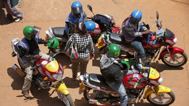 A woman in Rwanda surrounded by motorbike riders