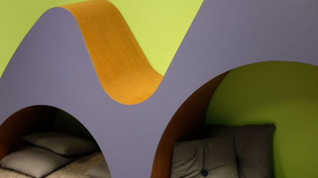 Clase con montañas de madera bajo las cuales hay espaciones para que los niños descansen o lean