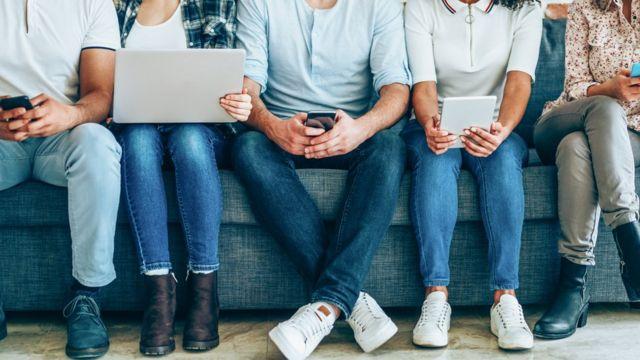 Personas sentadas con computadoras o celulares en sus manos
