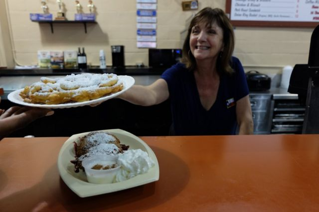 A woman behind a counter hands over a funnel cake in a paper plate