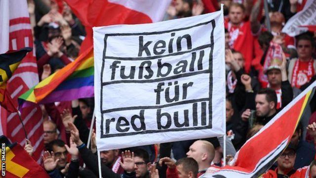 """مشجعو بايرن ميونيخ يحملون لافتة كتب عليها """"لا كرة قدم لـ ريد بُل"""""""