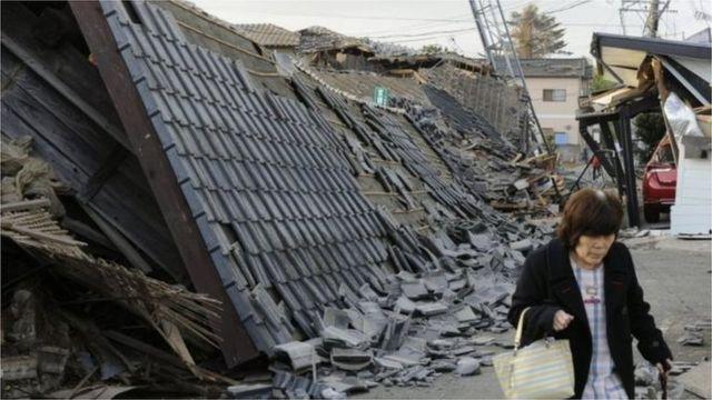 崩壊した家並みの横を歩く女性(15日)