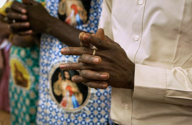Man's hands clasped in prayer