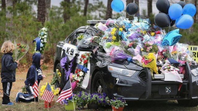 图中是几个小男孩为2018年4月在一次逮捕疑犯时不幸中枪殉职的麻塞诸塞州雅茅斯市警察肖恩·加农(Sean Gannon)献花致敬。
