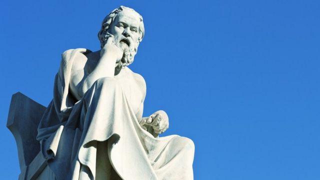 Estatua de Sócrates de mármol blanco con un fondo de cielo azul.