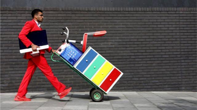 Foto mostra homem empurrando um arquivo e uma cadeira em um carrinho de mão