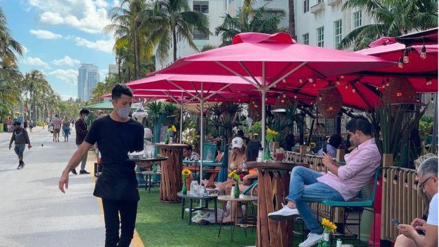 Camarero sirve mesas en Miami Beach.