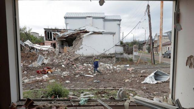 رجل يمر من أمام منزل تعرض للقصف في ستيباناكرات ، عاصمة إقليم ناغورنو كاراباخ.