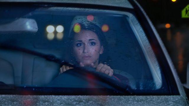 Mujer conduciendo de noche con cara de miedo.
