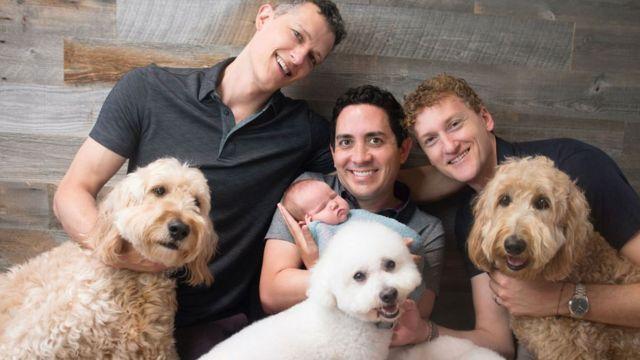 Ian Jenkins, Alan e Jeremy com bebê no colo e cachorros em volta
