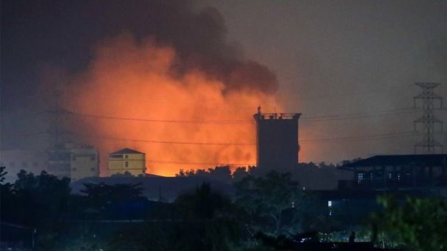 Burning Chinese-owned factories light up the industrial neighbourhood in Hlaing Tharyar, o­n the outskirts of Yangon, Myanmar, 15 March 2021