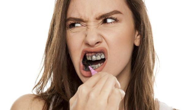 Una mujer se cepilla los dientes con una pasta dental a base de carbón.