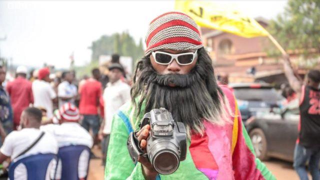 Mwanamume aliyevalia ndevu bandia nakamera ya video katika mji wa Arondizuogu wakati wa tamasha la keji Festival nchini Nigeria