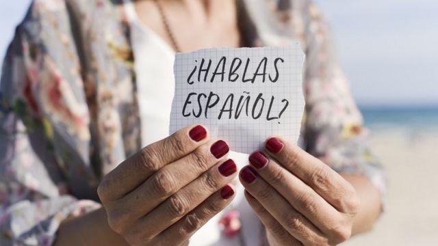 Una mujer sostiene un cartel que dice ¿hablas español?