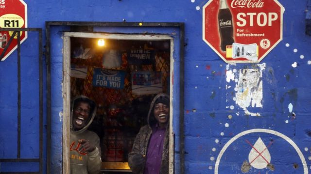 Men smile as they stand inside a shop hiding from rainfall, in Delft township on the outskirts of Cape Town, South Africa - Tuesday 26 July 2016