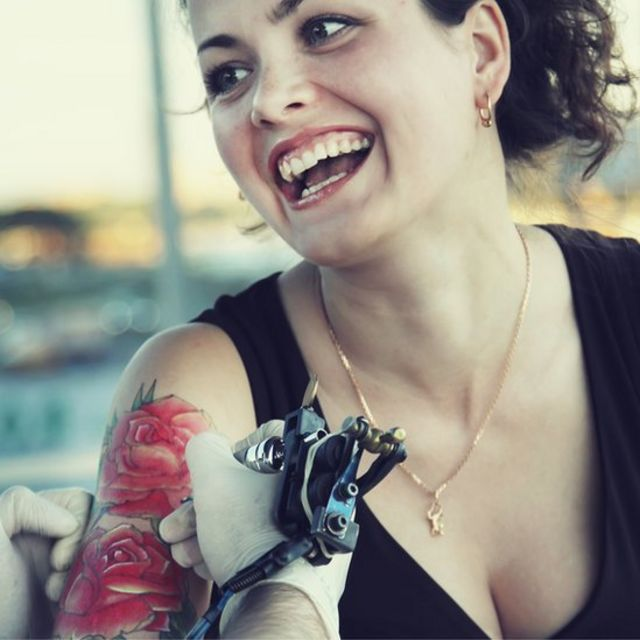 Mujer haciéndose tatuaje de flores rojas