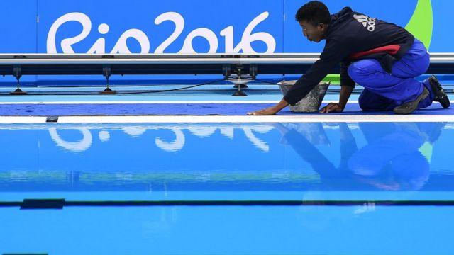 Un trabajador cuida los últimos detalles e la piscina antes del inicio de los juegos.