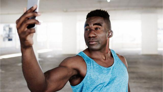 Man in sport gear taking a photo of himself