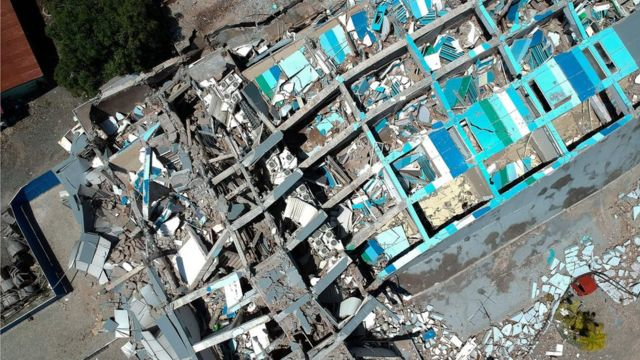 """This aerial picture shows the remains of a ten-storey hotel in Palu in Indonesia""""s Central Sulawesi on September 30, 2018 after it collapsed following a strong earthquake in the area."""
